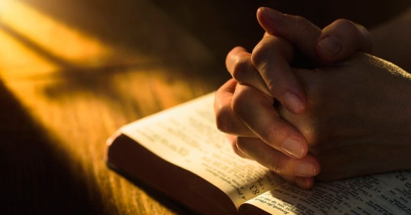 A Bible and praying hands